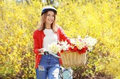 Menina e bicicleta bonitas novas com as flores na cesta Imagens de Stock