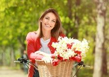 Menina e bicicleta bonitas novas com as flores na cesta no parque Imagens de Stock