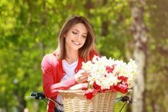 Menina e bicicleta bonitas novas com as flores na cesta no parque Fotos de Stock