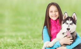 Menina e cão de puxar trenós Siberian na grama verde Fotografia de Stock Royalty Free