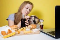 Menina e cão que comem o fast food imagens de stock royalty free