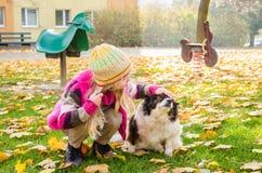 Menina e cão que jogam no campo de jogos Fotografia de Stock Royalty Free