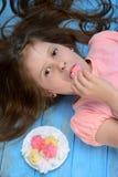 Menina e cookies francesas coloridas da merengue da baunilha Imagens de Stock