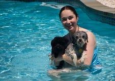Menina e dois cães em uma piscina Fotografia de Stock Royalty Free