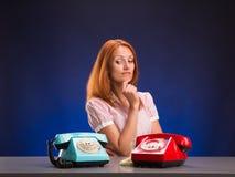 Menina e dois telefones Imagens de Stock