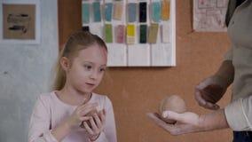 Menina e homem do Ceramist que guardam a argila nas mãos e que fazem o earthenwa filme