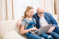 Menina e homem superior nos monóculos usando o portátil no sofá Fotografia de Stock Royalty Free