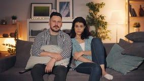 Menina e indivíduo que olham o filme assustador na tevê que senta-se no sofá no apartamento junto