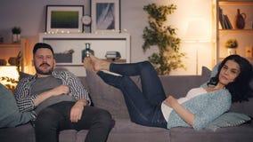 Menina e indivíduo que olham a tevê no apartamento no sofá que aprecia mass media junto filme