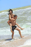 Menina e indivíduo na praia Fotografia de Stock