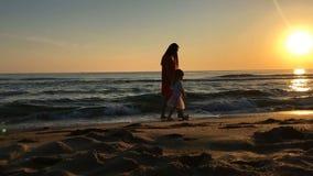 Menina e jovem mulher que andam ao longo da praia video estoque