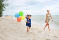 Menina e mãe asiáticas da criança na praia com balões coloridos foto de stock royalty free