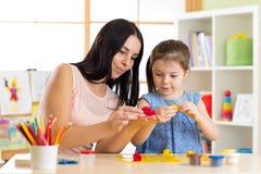 A menina e a mãe da criança da criança jogam brinquedos coloridos da argila no berçário em casa fotografia de stock royalty free