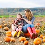 Menina e mãe da criança que têm o divertimento na abóbora Fotos de Stock Royalty Free