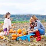 Menina e mãe da criança que têm o divertimento no campo da abóbora Fotos de Stock Royalty Free