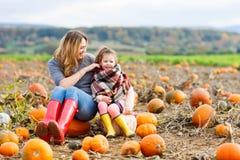 Menina e mãe da criança que têm o divertimento no campo da abóbora Fotografia de Stock Royalty Free