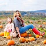 Menina e mãe da criança que têm o divertimento no campo da abóbora Foto de Stock Royalty Free