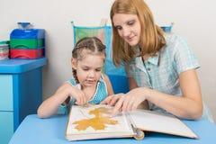 A menina e a mãe de cinco anos estão considerando o herbário das folhas no álbum Fotos de Stock Royalty Free