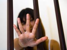 Menina e mão asiáticas atrás das barras fotografia de stock