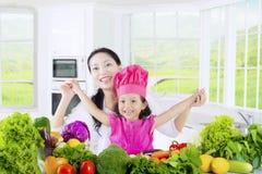 Menina e mamã alegres com vegetal Fotos de Stock Royalty Free