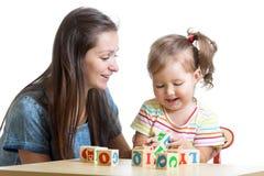 A menina e a mamã da criança têm o divertimento que joga brinquedos dos cubos fotos de stock royalty free