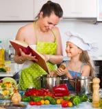 Menina e mamã com livro de cozinha Foto de Stock Royalty Free