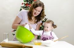 A menina e a matriz estão preparando bolinhos Fotos de Stock Royalty Free