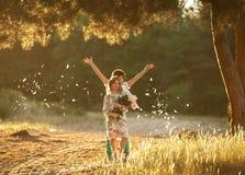 Menina e menino alegres pequenos na clareira ensolarada Fotos de Stock Royalty Free