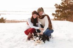 Menina e menino bonitos com o cão ronco na floresta do inverno Fotografia de Stock Royalty Free