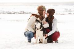 Menina e menino bonitos com o cão ronco na floresta do inverno Fotografia de Stock
