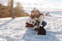 Menina e menino bonitos com o cão ronco na floresta do inverno Fotos de Stock