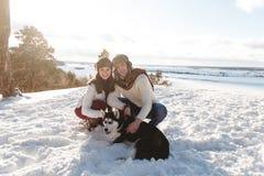 Menina e menino bonitos com o cão ronco na floresta do inverno Imagem de Stock
