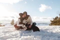 Menina e menino bonitos com o cão ronco na floresta do inverno Foto de Stock Royalty Free