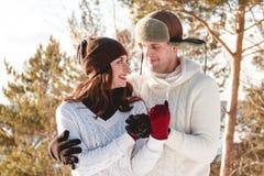 Menina e menino bonitos com o cão ronco na floresta do inverno Foto de Stock