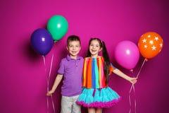 Menina e menino com os balões no fundo da cor Celebração do aniversário Fotos de Stock