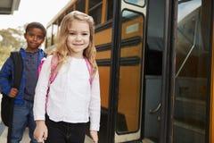 Menina e menino da escola primária que esperam para embarcar o ônibus escolar imagem de stock