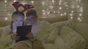Menina e menino de sorriso com o computador do PC da tabuleta que senta-se no sofá em casa no fundo de decorações do Natal video estoque