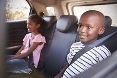 Menina e menino de sorriso na parte de trás do carro na viagem por estrada da família fotos de stock royalty free