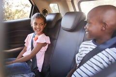 Menina e menino de sorriso que olham se no carro em uma viagem fotografia de stock