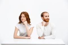 Menina e menino do ruivo de Tenderless que sentam-se na mesa branca fotografia de stock royalty free