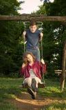 Menina e menino em um balanço que tem o divertimento Foto de Stock