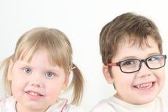 Menina e menino louros pequenos felizes em sorrisos dos vidros Imagem de Stock Royalty Free