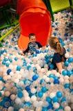Menina e menino no parque de diversões interno do divertimento Imagens de Stock Royalty Free