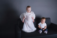 Menina e menino no vestido do anjo Imagens de Stock