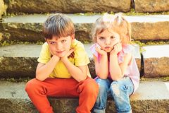 Menina e menino pequenos em escadas rela??es F?rias de ver?o A inf?ncia ama primeiramente pares de crian?as pequenas menino trist imagens de stock