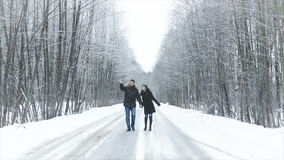 Menina e menino que andam ao longo da estrada nas madeiras Guarde as mãos Beijam video estoque