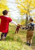 Menina e menino que andam com seu brinquedo favorito o coelho imagens de stock royalty free