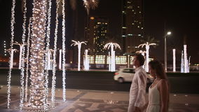 Menina e menino que andam na rua a noite Dubai Entre as árvores de palmas de incandescência filme