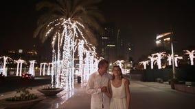 Menina e menino que andam na rua a noite Dubai Entre as árvores de palmas de incandescência UAE video estoque