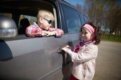 Menina e menino que conduzem o carro dos pais Imagens de Stock